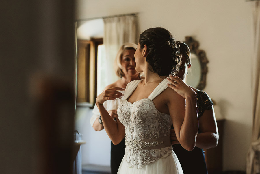 tuscany intimate wedding detail bride finishing to dress
