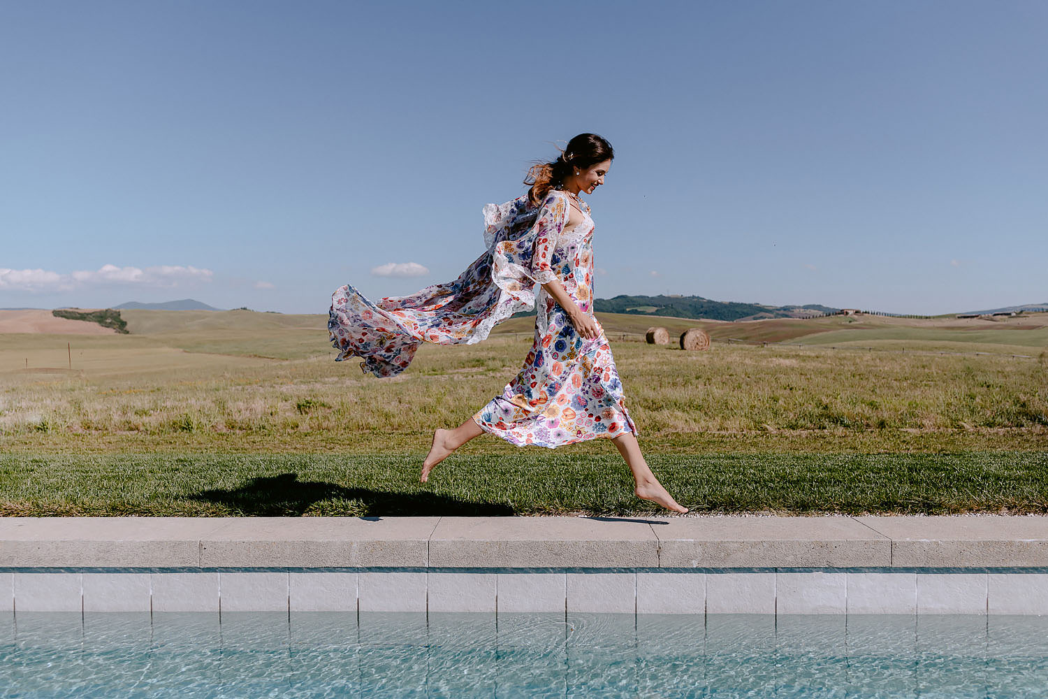 editorial Intimate Wedding Inspiration in Tuscan Rolling Hills bride in petticoat flying on pool