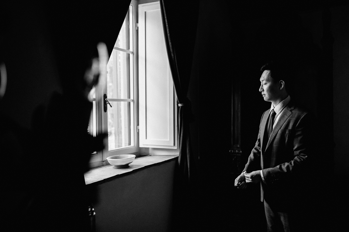 groom getting ready in dramatic light